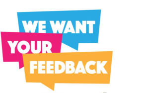 "Words ""We Want Your Feedback"" on blue, pink, and yellow signs"